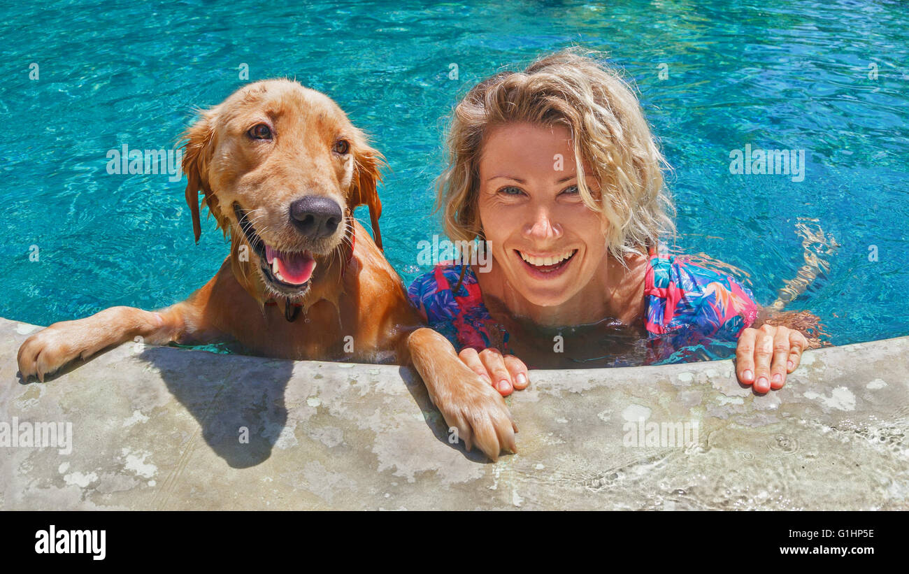 Funny portrait of smiling woman playing with dog and training golden retriever puppy in blue swimming pool. - Stock Image