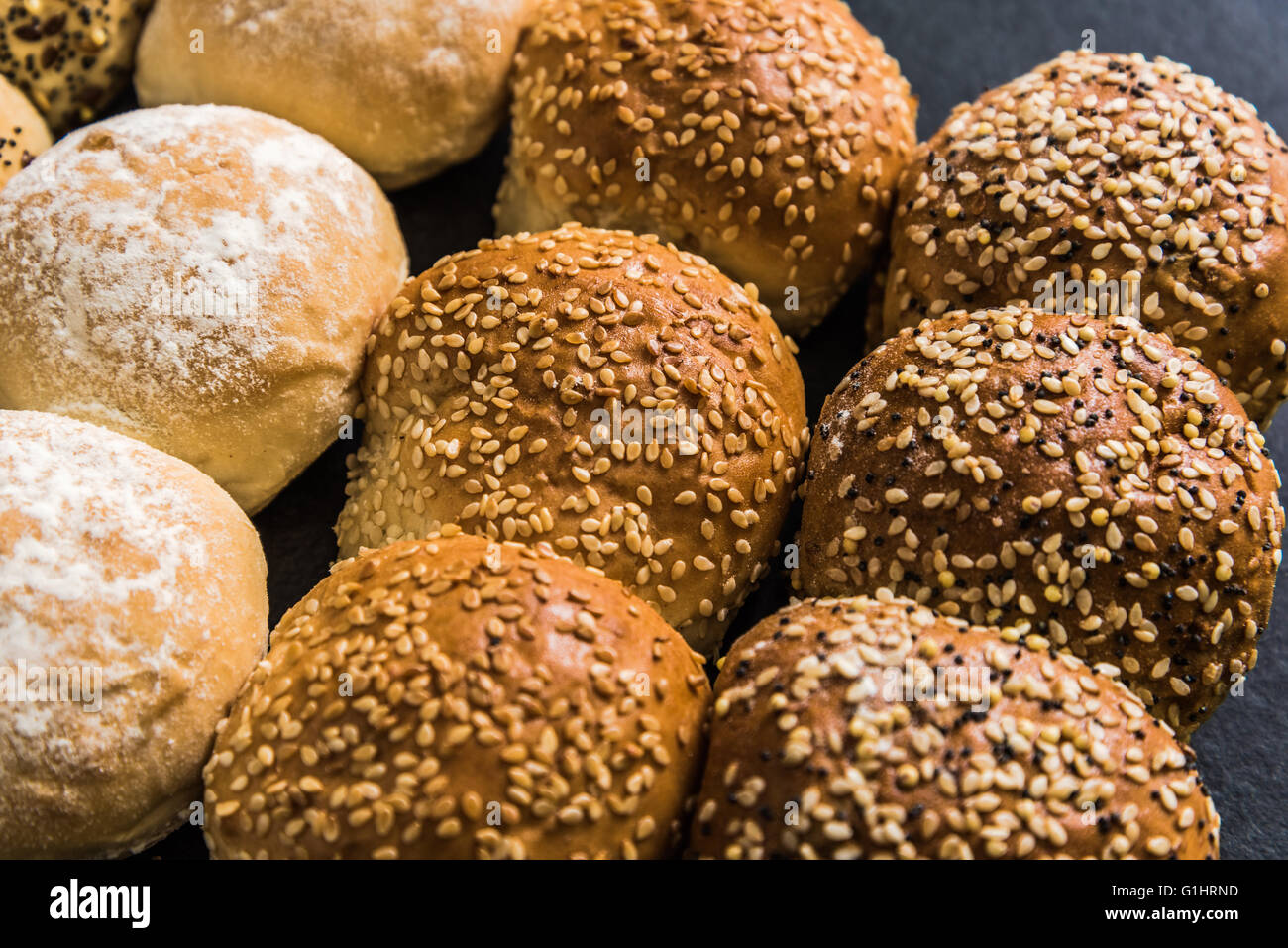 Artisan bakery buns and rolls on dark slate background from above - Stock Image