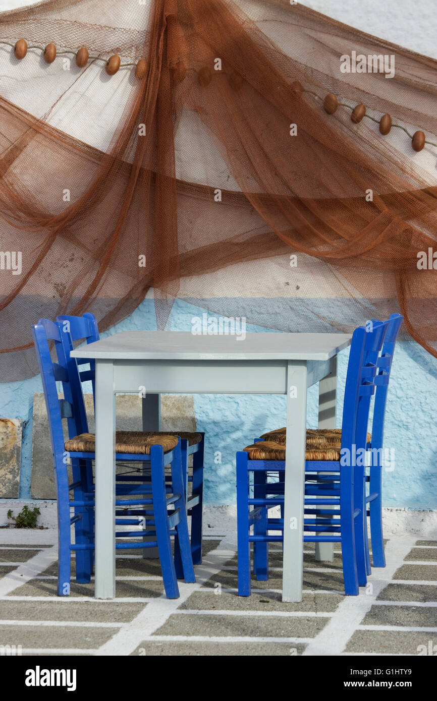 set of blue chairs cyan empty tavern table on chequered floor hanging fishing nets wall decorationmyrina limnos greece