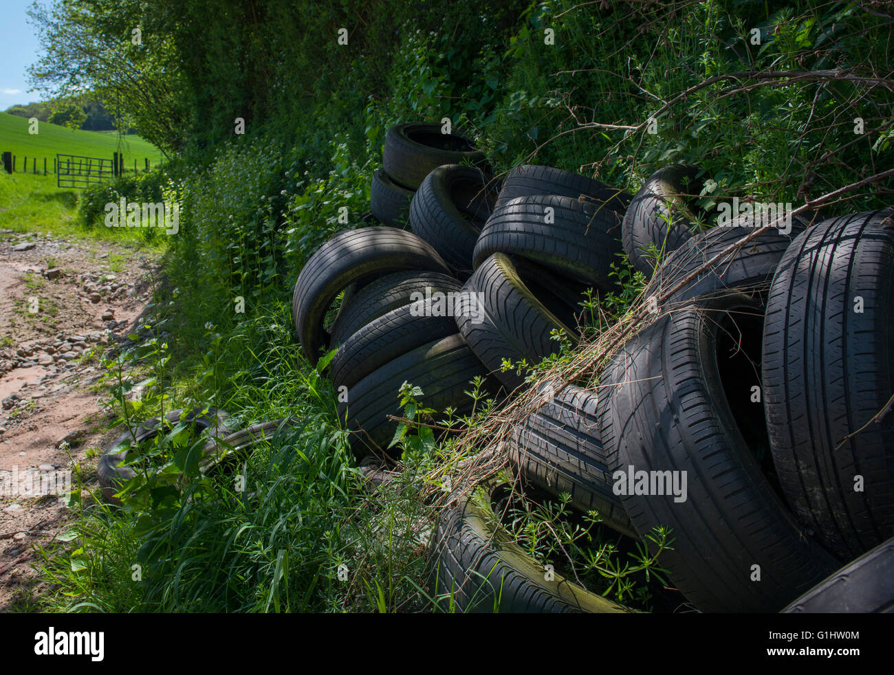 A pile of tyres next to a farm track in Shropshire, England, UK. - Stock Image