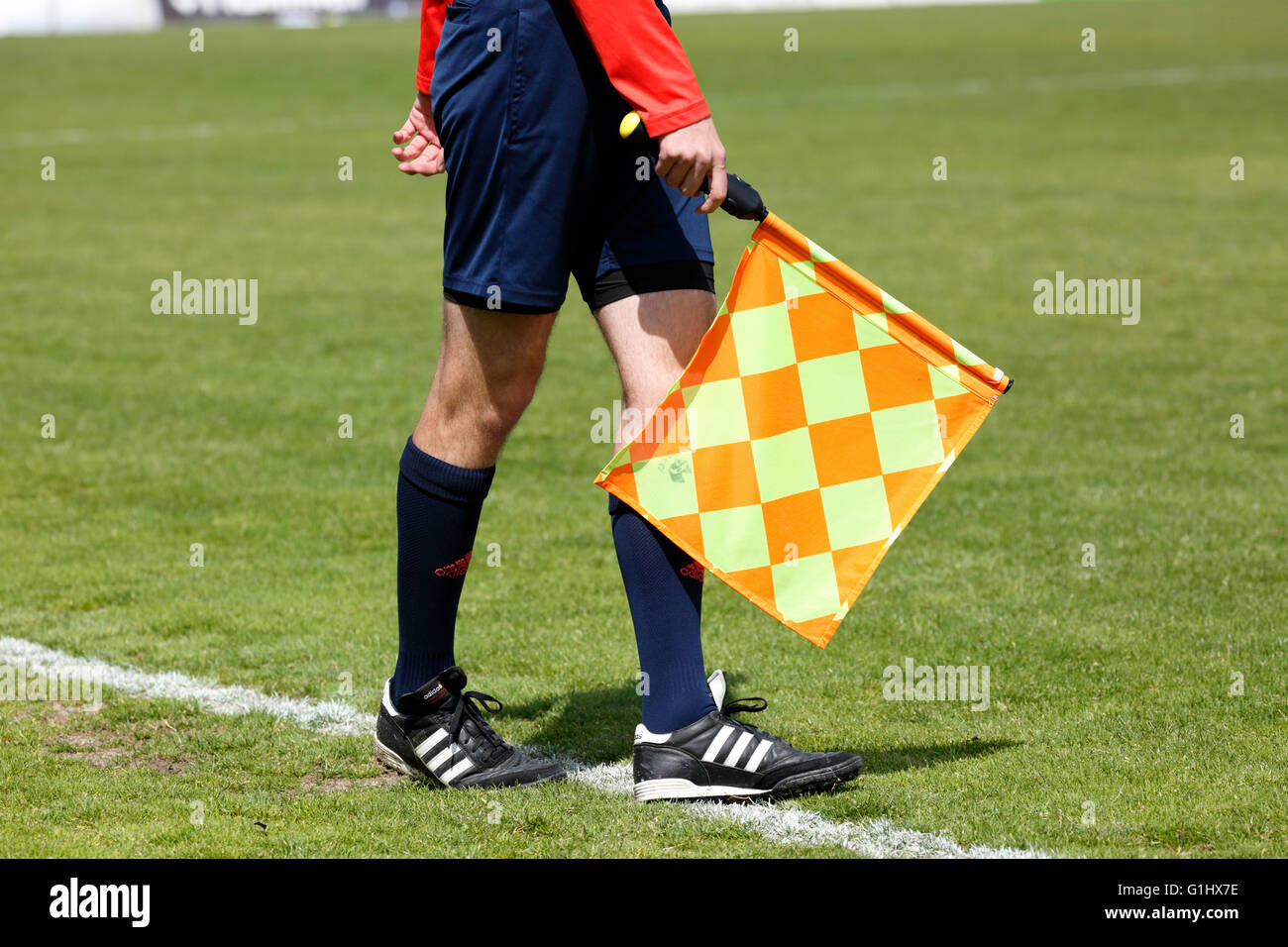 sports, football, symbolism, assistant referee, linesman with flag at the touchline - Stock Image
