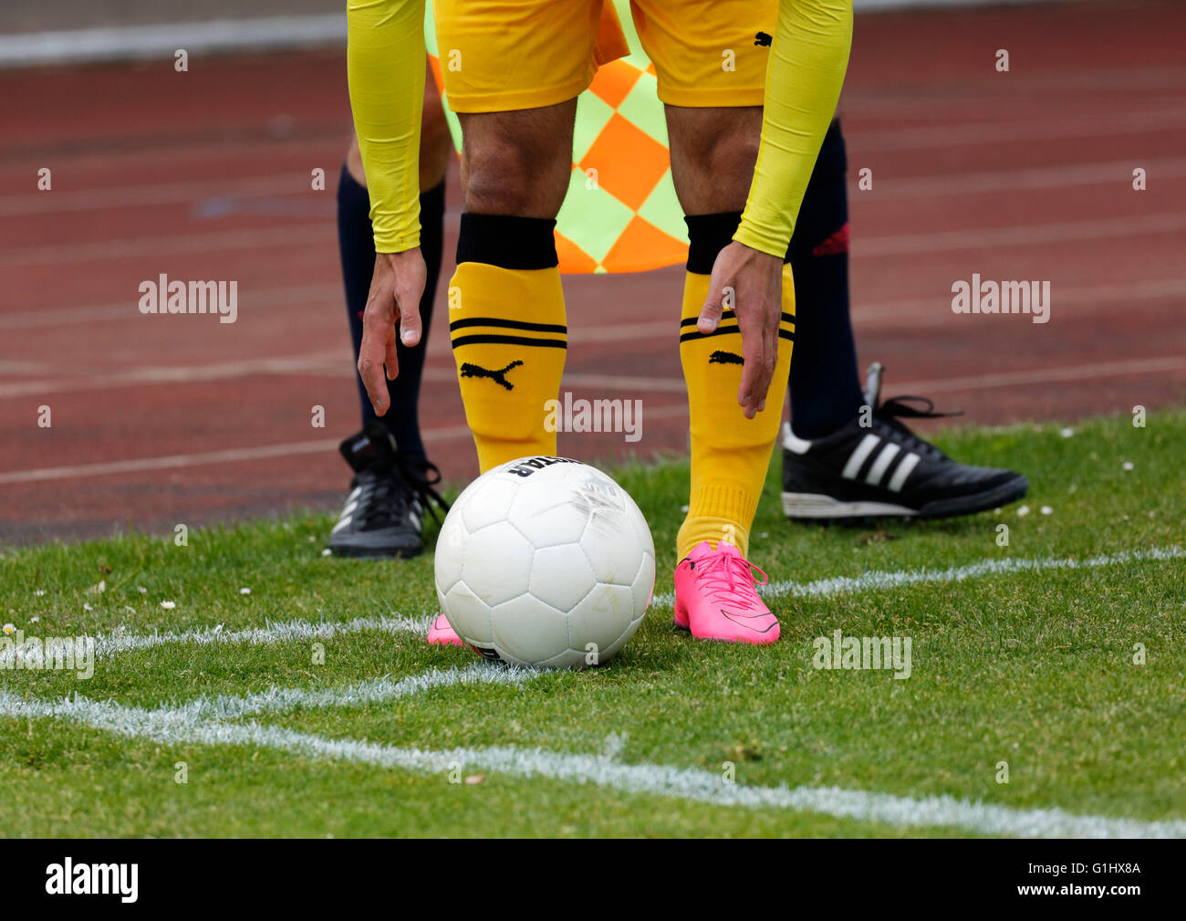 sports, football, symbolism, footballer legs, player puts the ball on the corner mark for a corner kick, behind - Stock Image