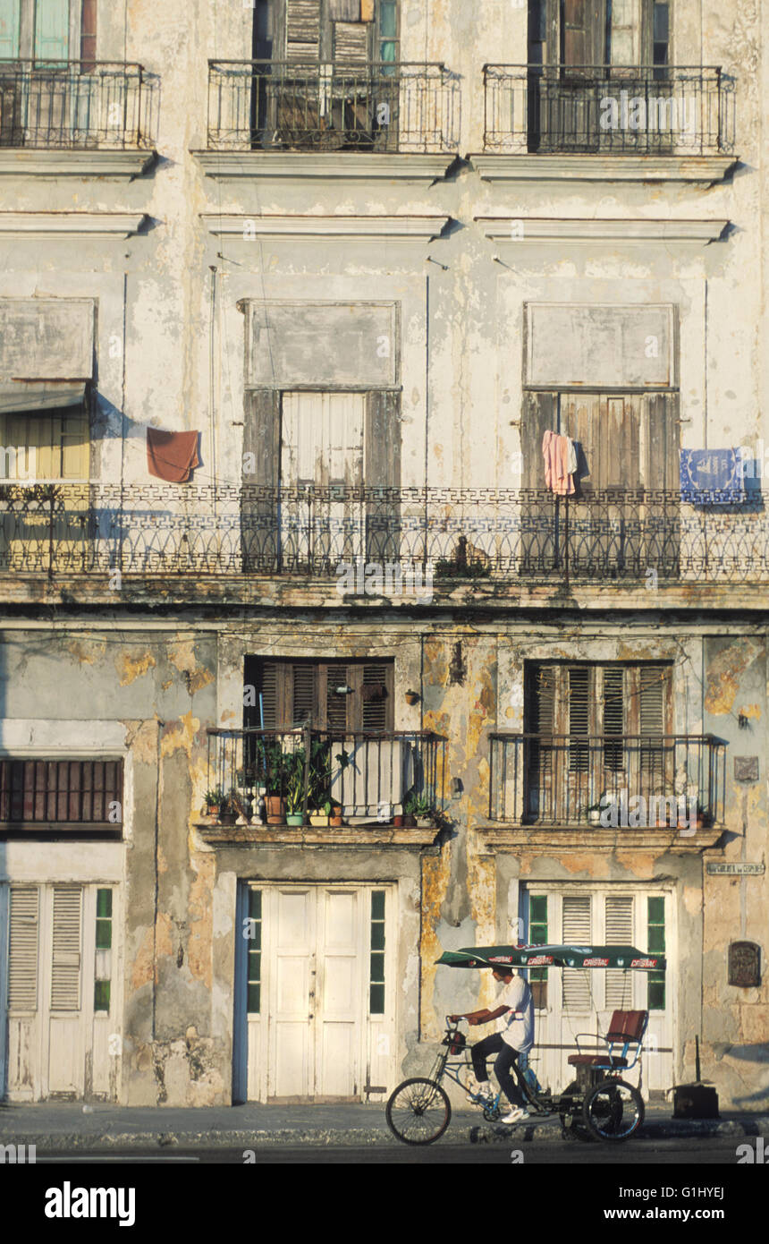 bicycle taxi in Old Havana and facade of dilapidated apartment building downtown Havana Cuba Caribbean - Stock Image