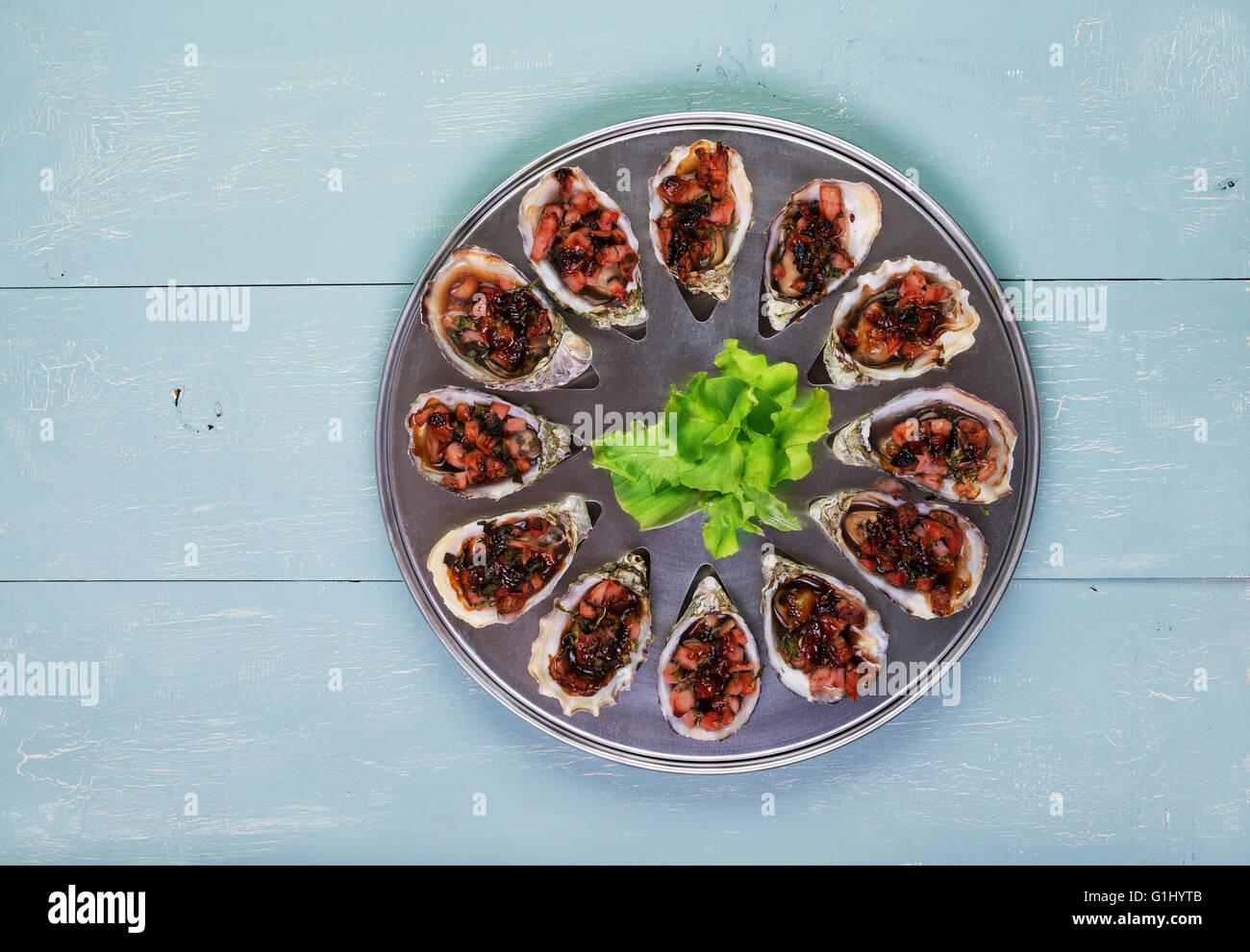 Oven baked oysters kilpatrick on special cooking and serving metal tray - Stock Image