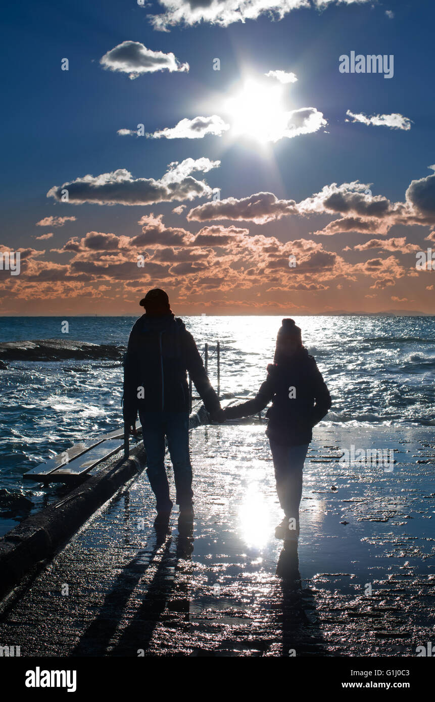 two people watching the sunset who goes to sleep in the sea - Stock Image
