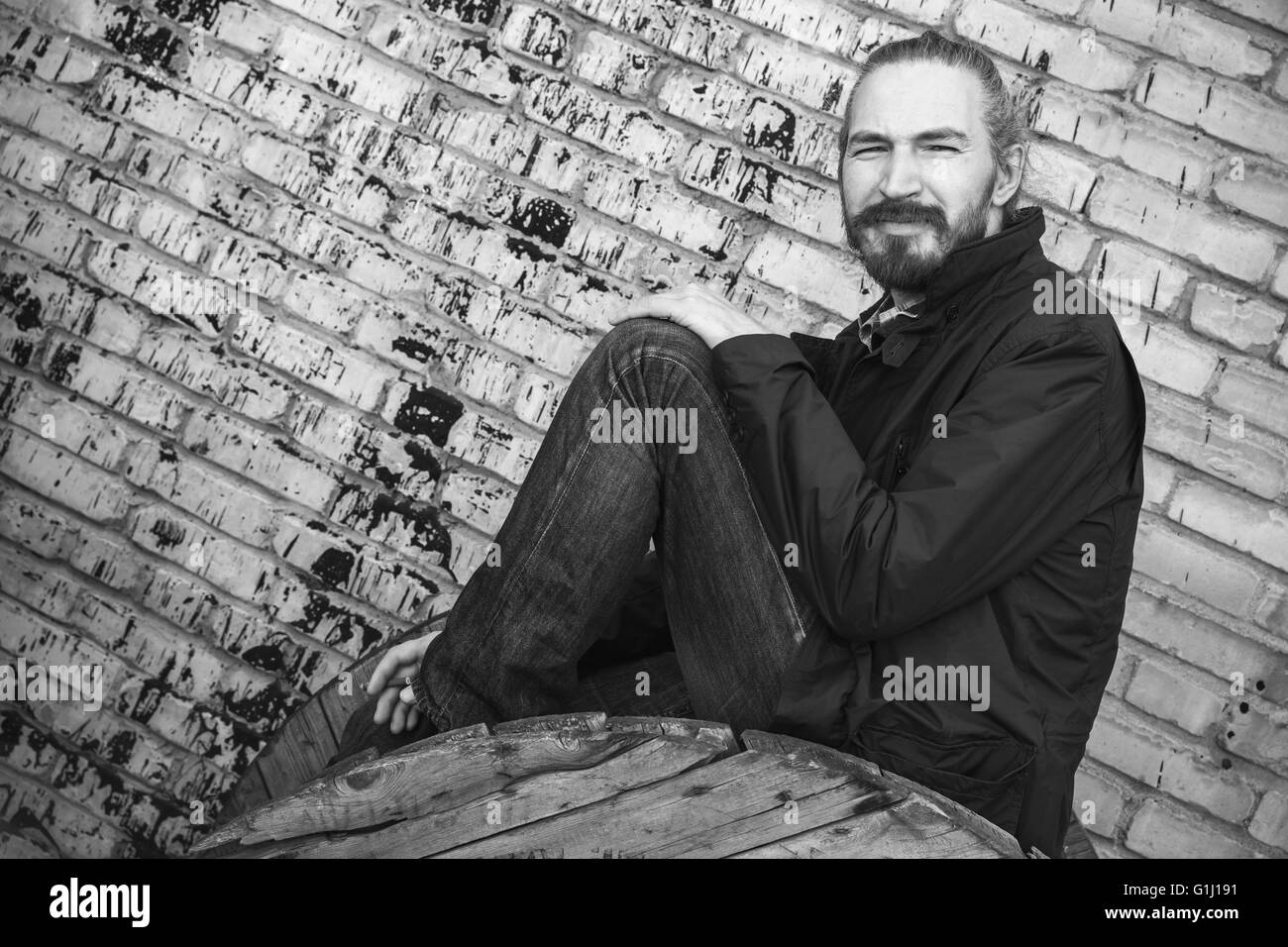 Outdoor portrait of young bearded Asian man in black over gray urban grungy brick wall background, black and white - Stock Image