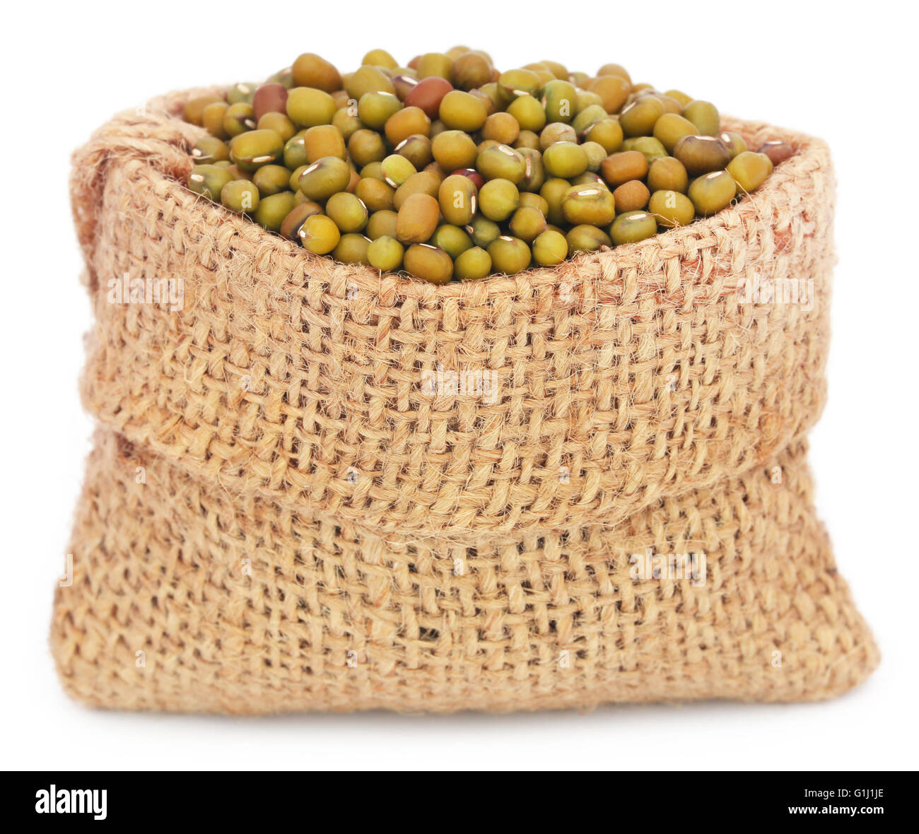 Mung beans in jute bag over white background - Stock Image