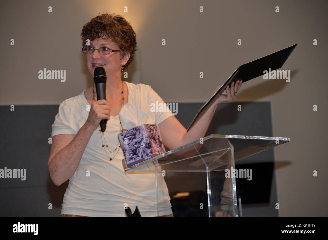 woman speaker holds a folder while speaking - Stock Image