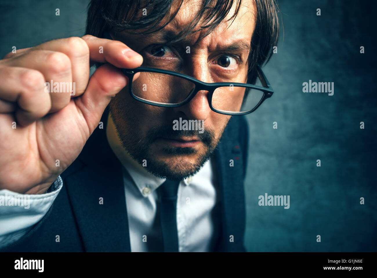 Angry tax inspector looking serious and determined, adult businessperson with glasses - Stock Image