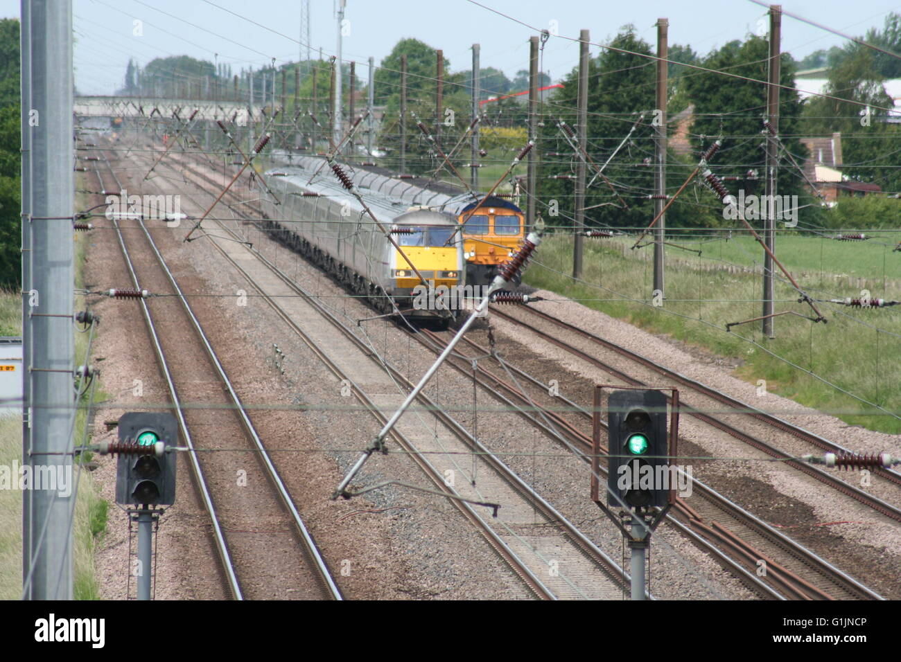 East Coast Main Line Passenger and Freight Trains head south at Skelton ECML - Stock Image