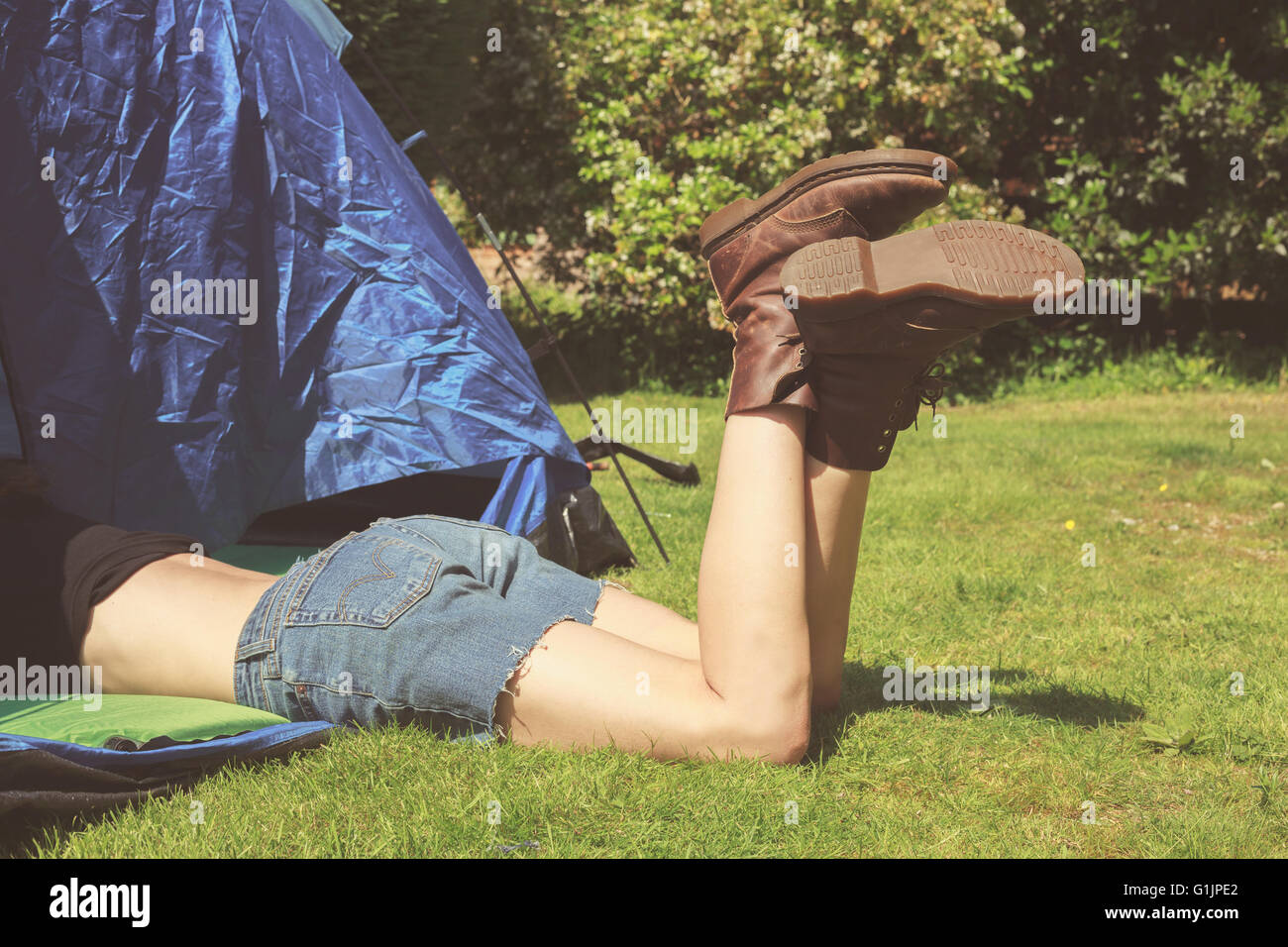 A young woman is lying in a tent with her legs sticking out - Stock Image