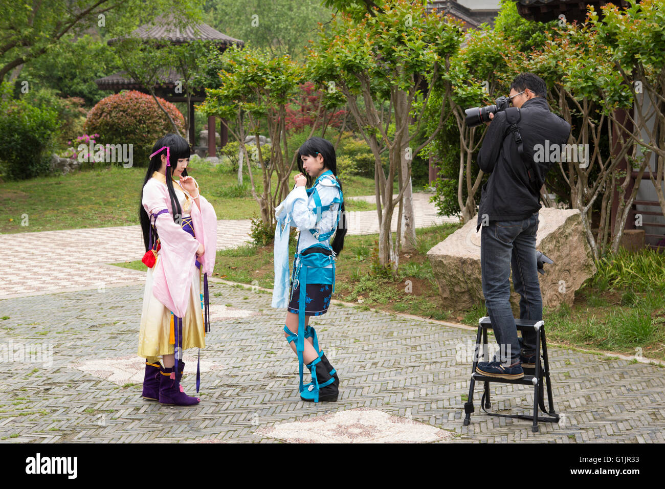 Scene with Chinese photographer at work with two cosplay photo models at Xuanwu Park, youth culture in Nanjing, - Stock Image