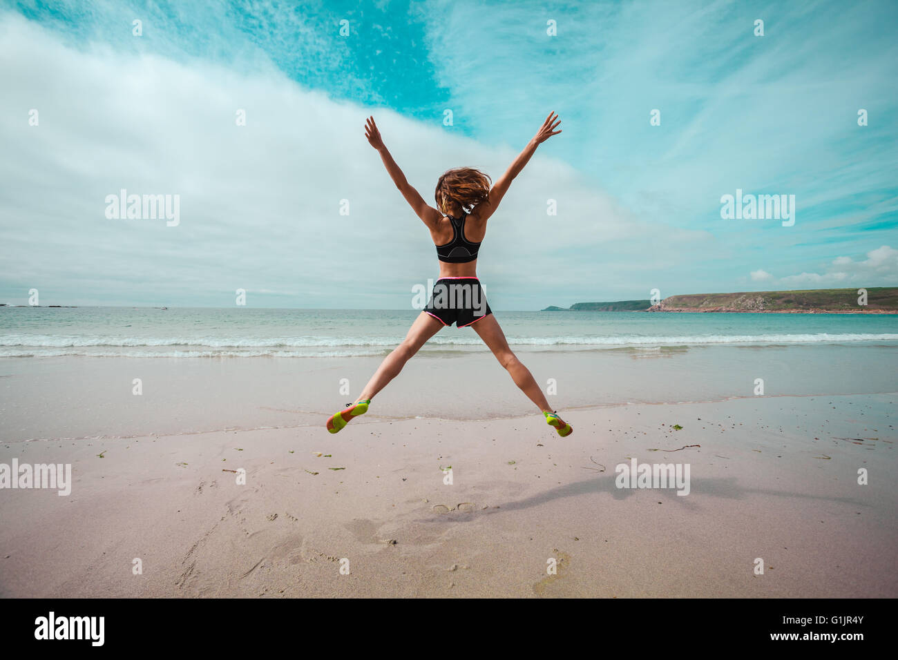 A young woman is doing star jumps on the beach by the sea - Stock Image