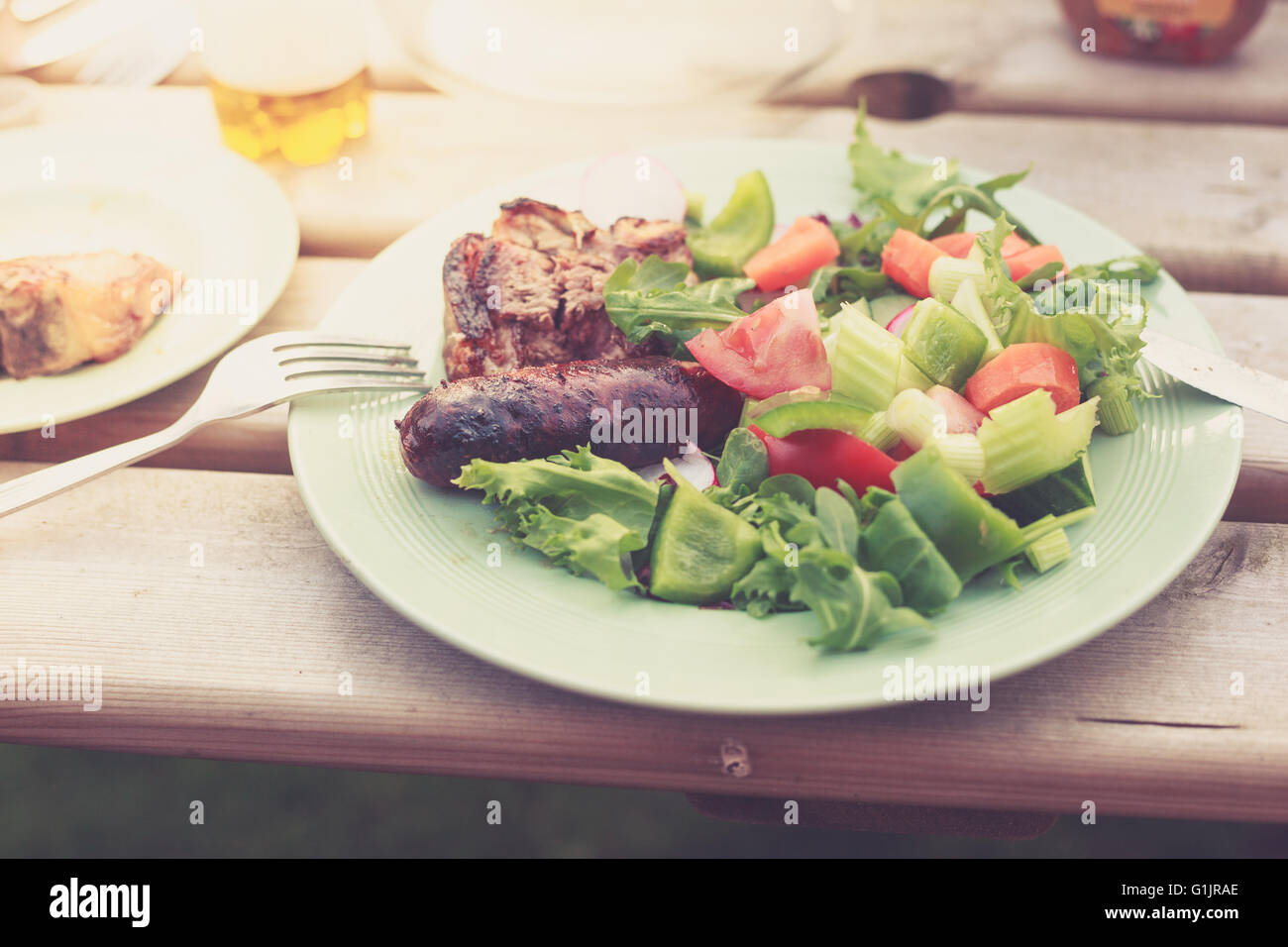 A plate with salad and freshly barbecued meat on a table outside on a sunny day - Stock Image