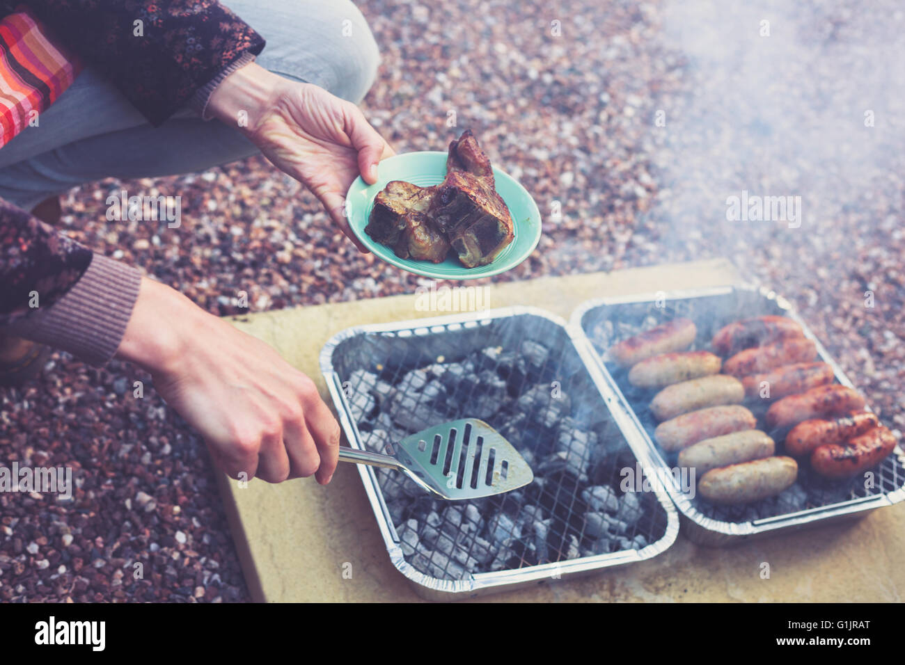 A young woman is cooking meat on a barbecue - Stock Image