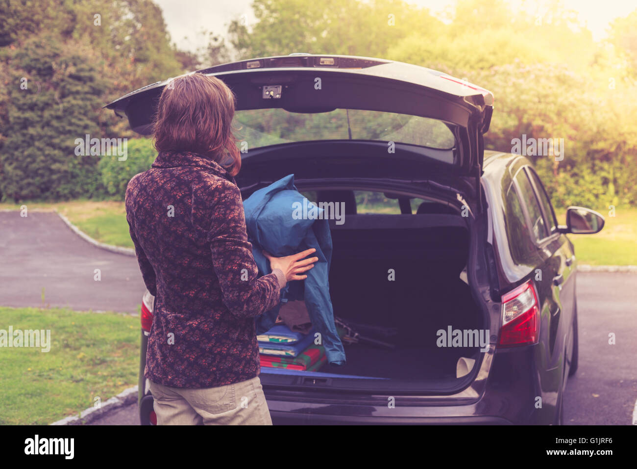 A young woman is opening the trunk of a car - Stock Image