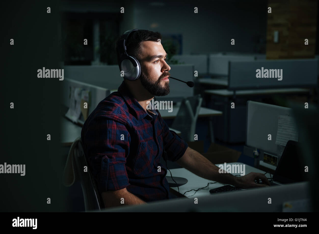 Concentrated handsome young man in headphones sitting and working at night in dark office - Stock Image
