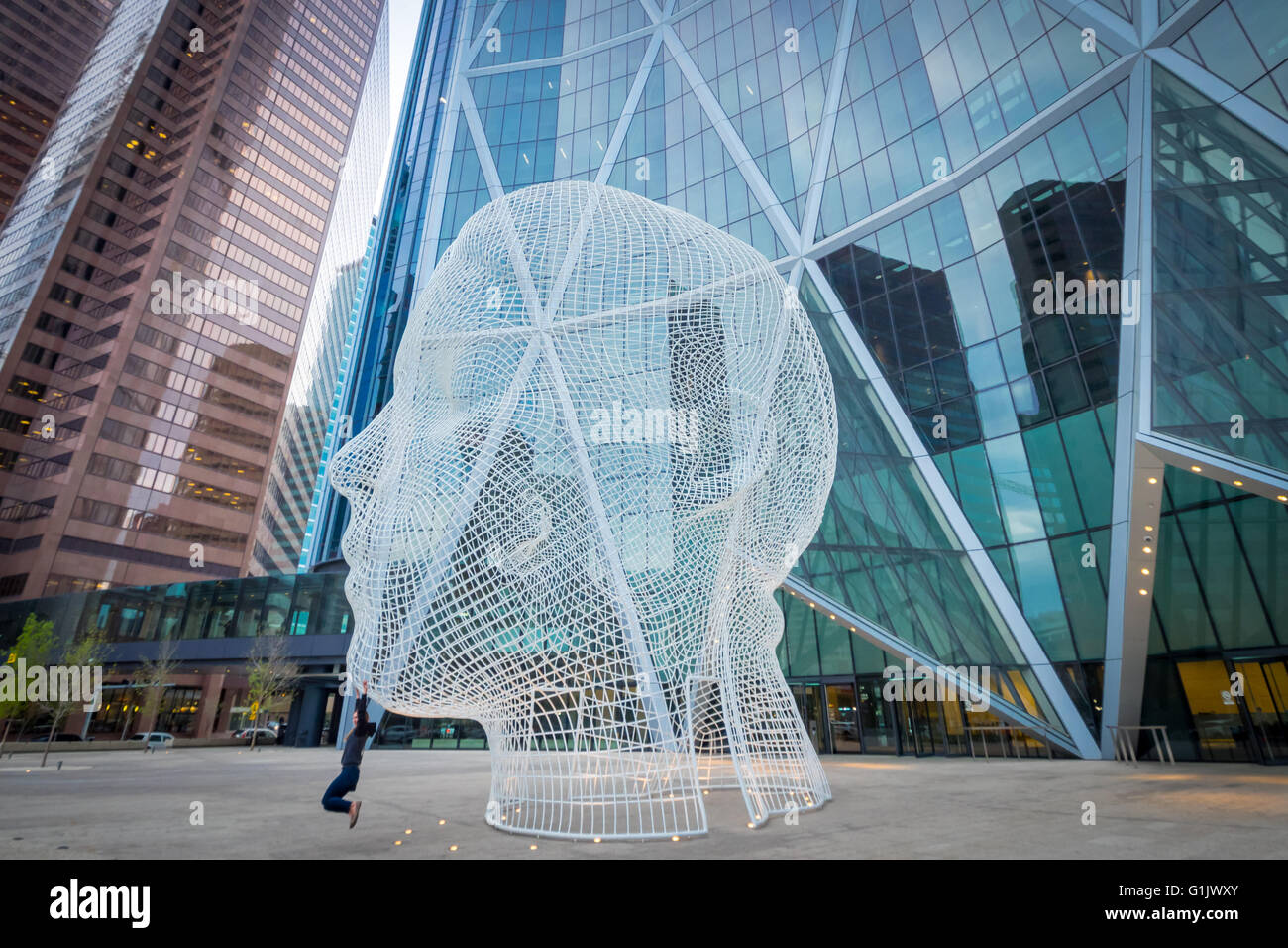 A view of the sculpture Wonderland by Jaume Plensa, in front of The Bow skyscraper in Calgary, Alberta, Canada. - Stock Image