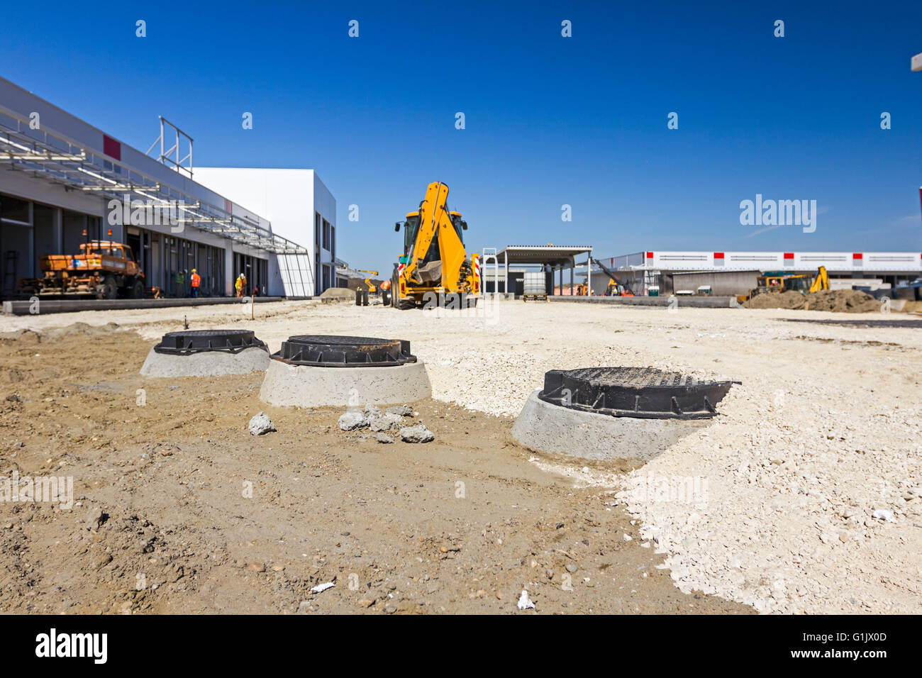 Close up of new metal cover over concrete manhole at construction site. - Stock Image