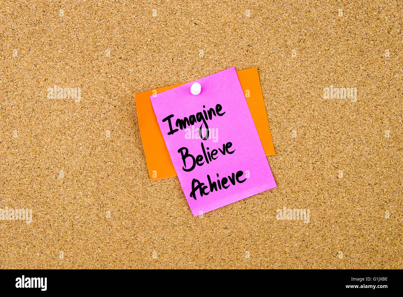Imagine Believe Achieve written on paper note pinned on cork board with white thumbtack, copy space available - Stock Image