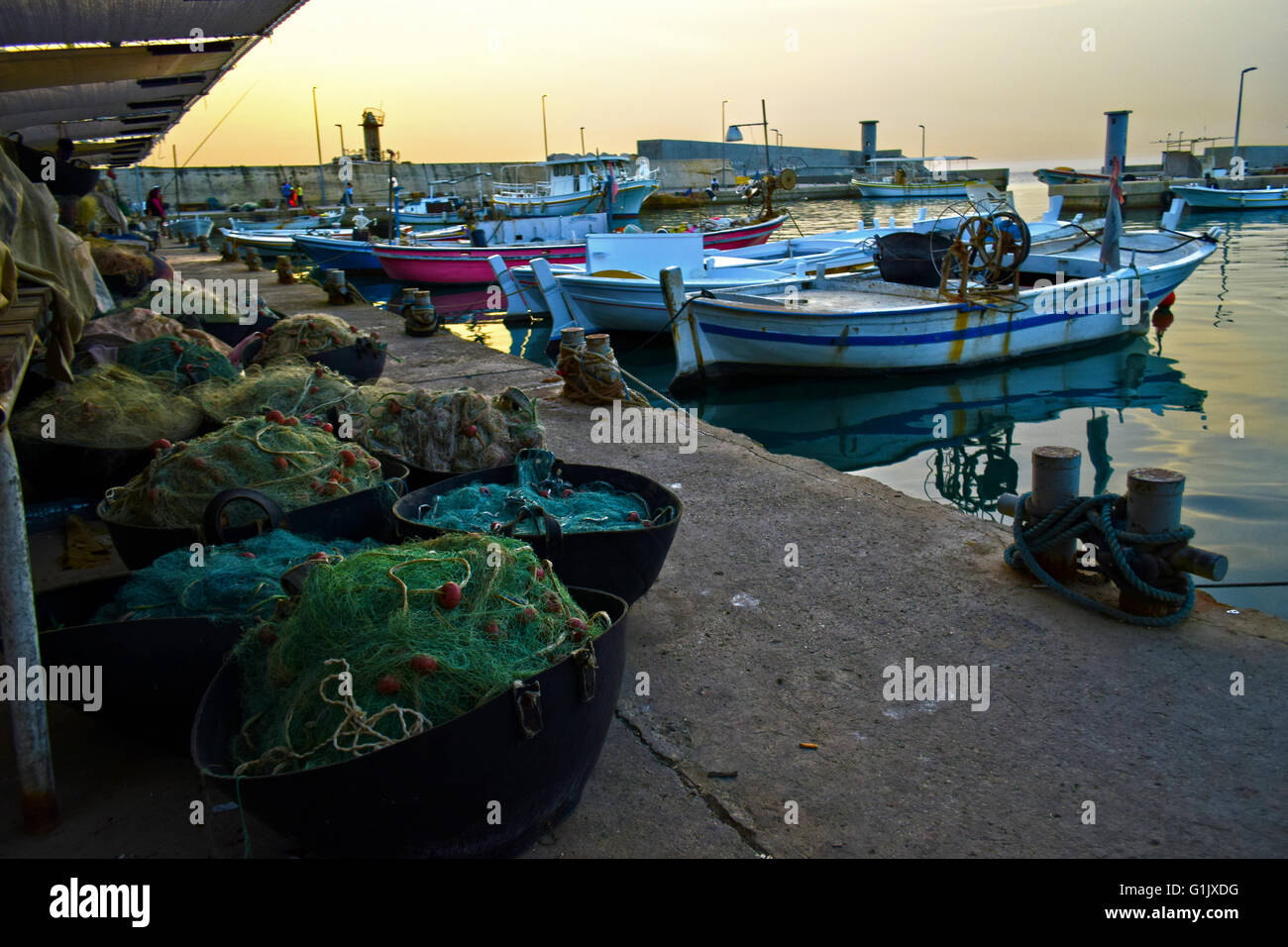 the old nets of the fisherman, the ships and a calm peaceful sunset. - Stock Image
