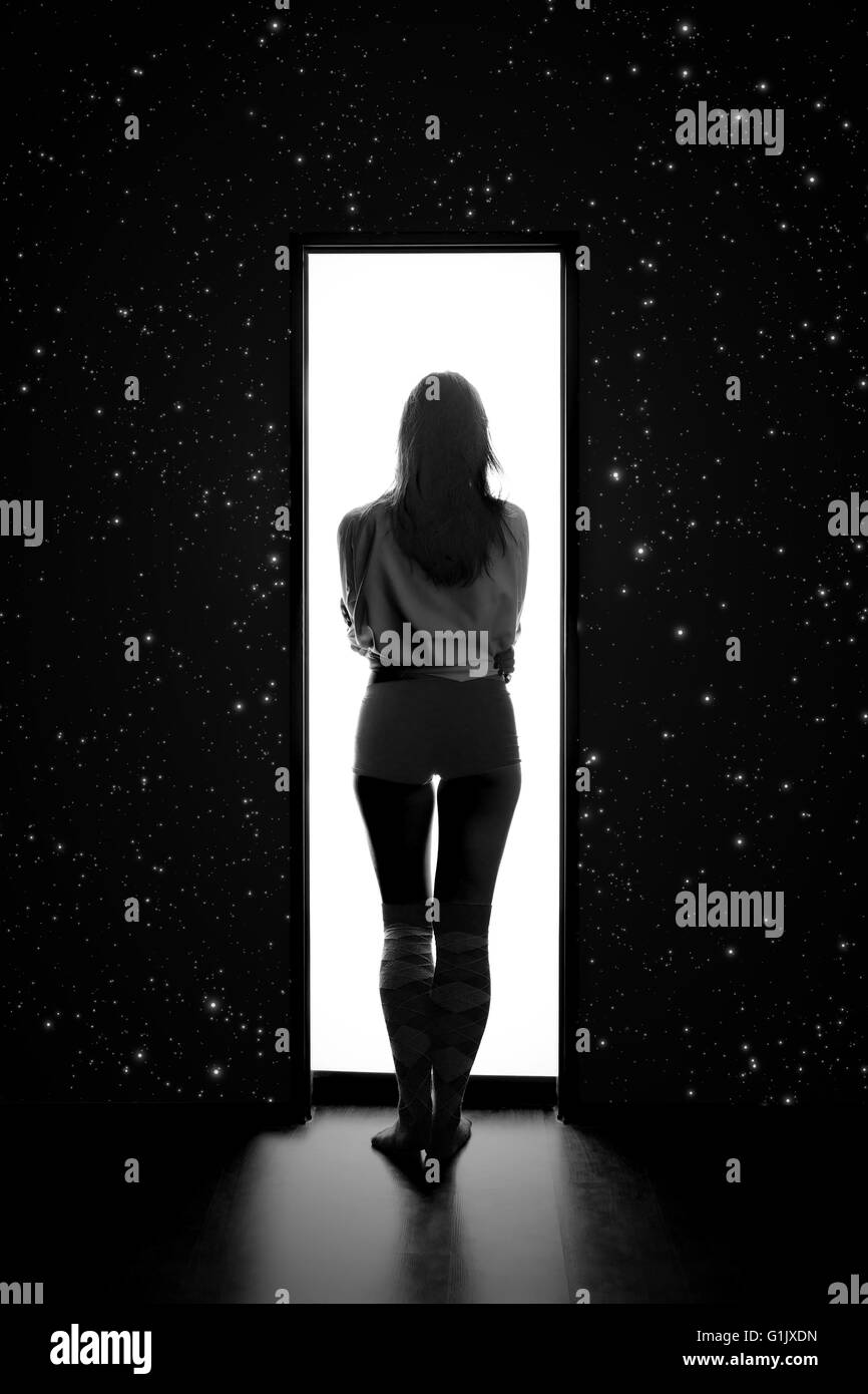 woman enter to white space from dark with stars, monochrome image - Stock Image