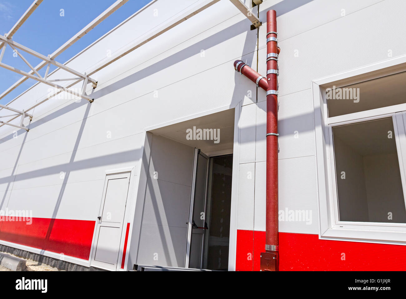 Unfinished red rain drain pipe for gutter on new building. Stock Photo