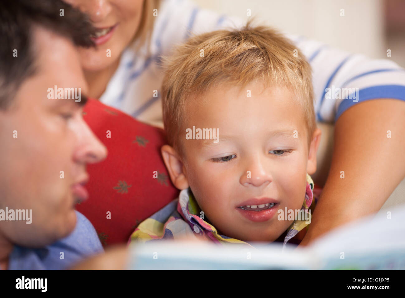 Cute little boy reading a book with his parents - Stock Image
