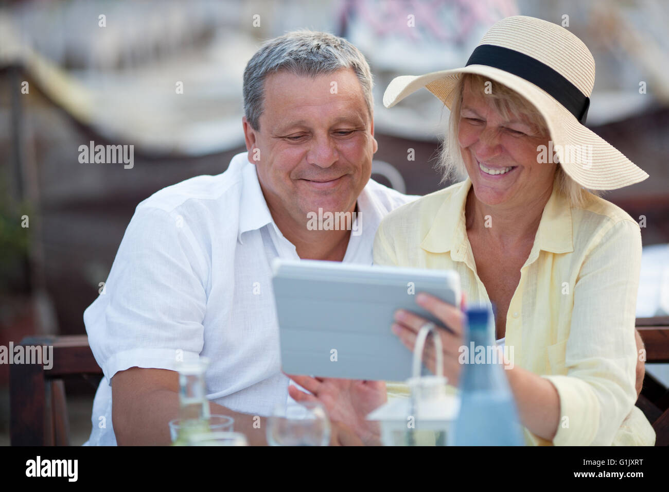 Smiling middle-aged couple using a tablet - Stock Image