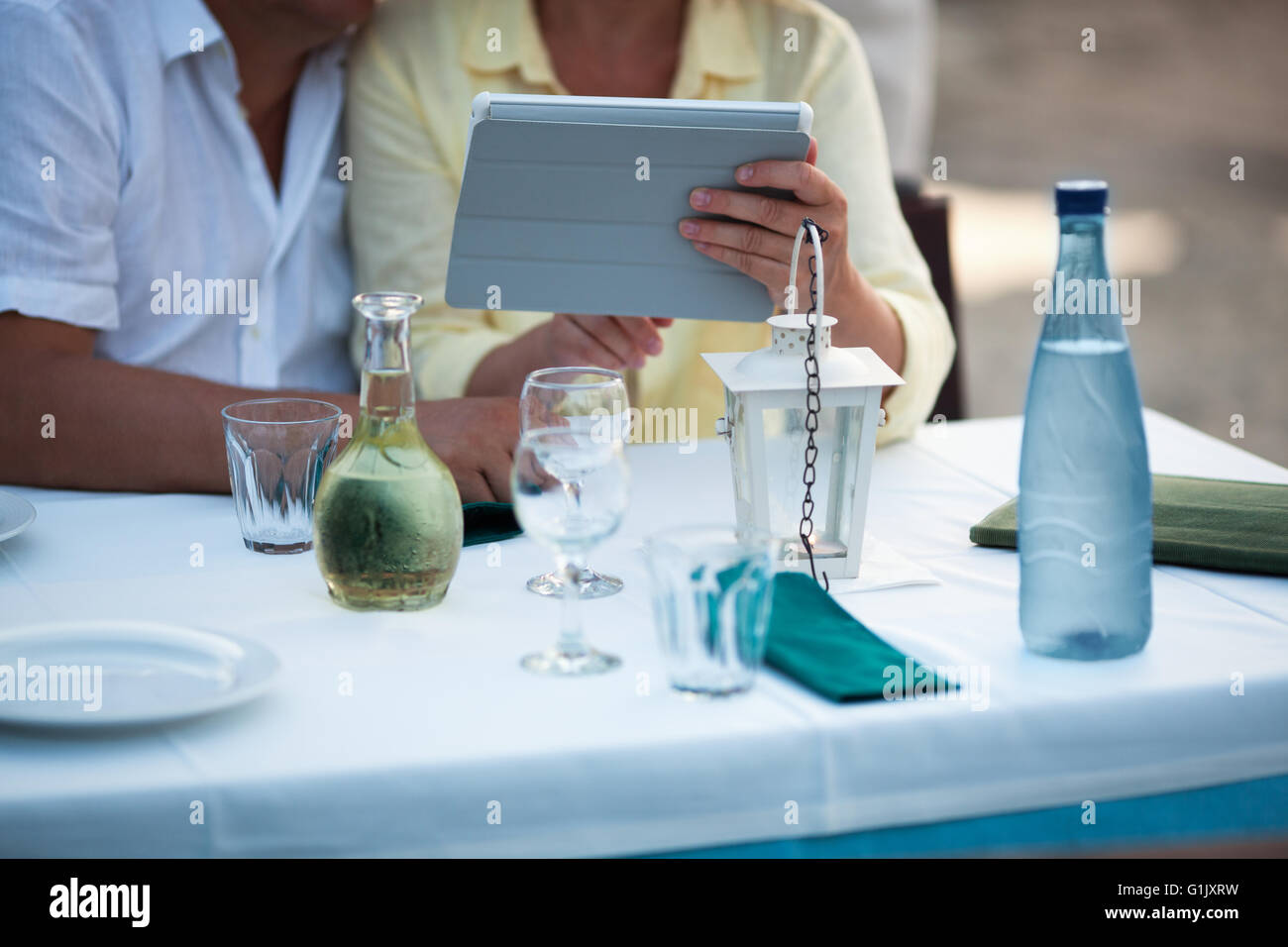 Middle-aged couple using a tablet at the table - Stock Image