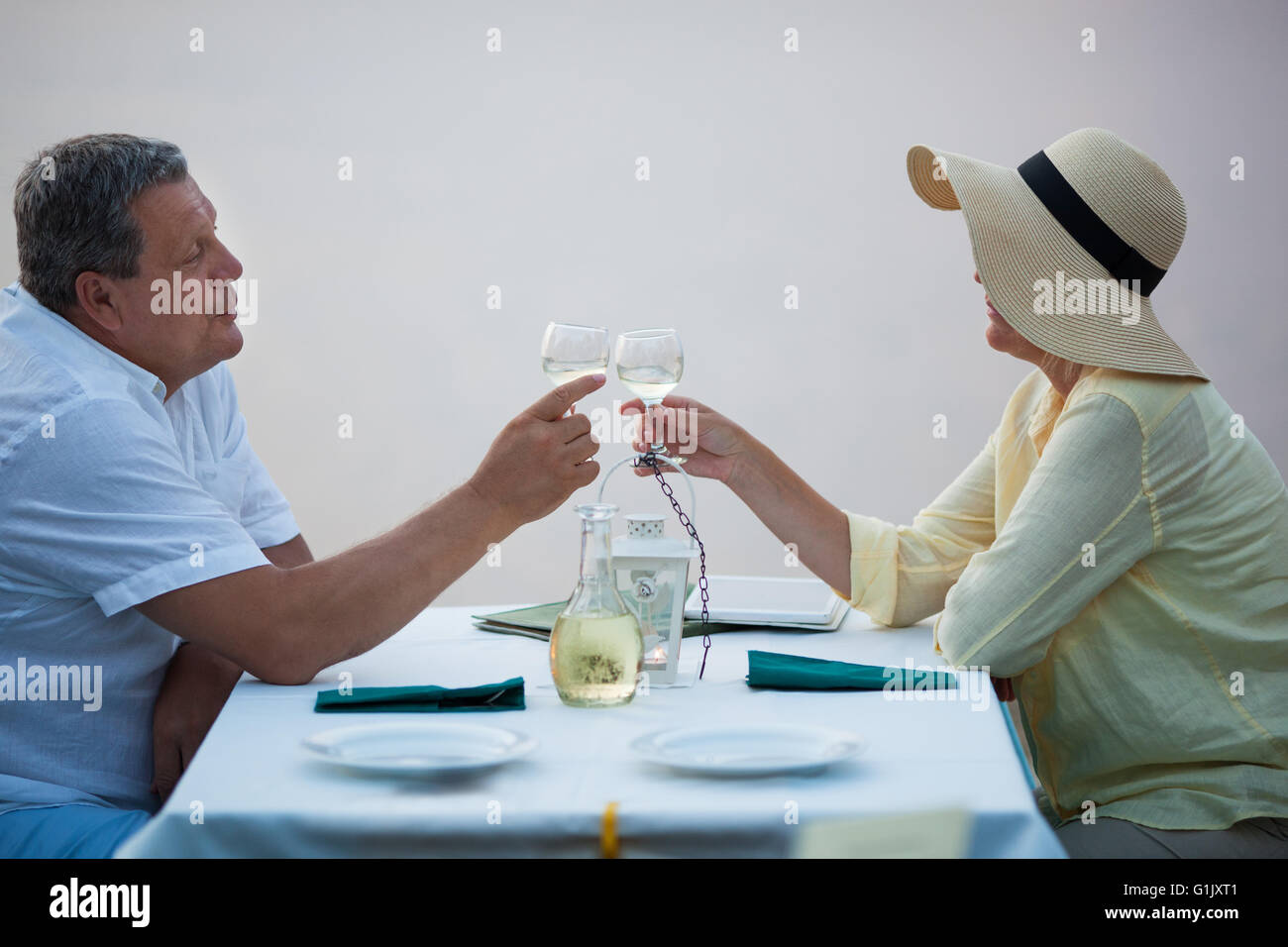 Romantic middle-aged couple toasting each other - Stock Image