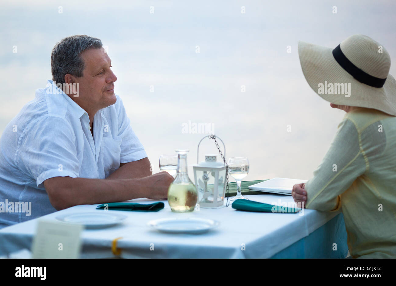 Middle-aged couple sitting waiting for a meal - Stock Image