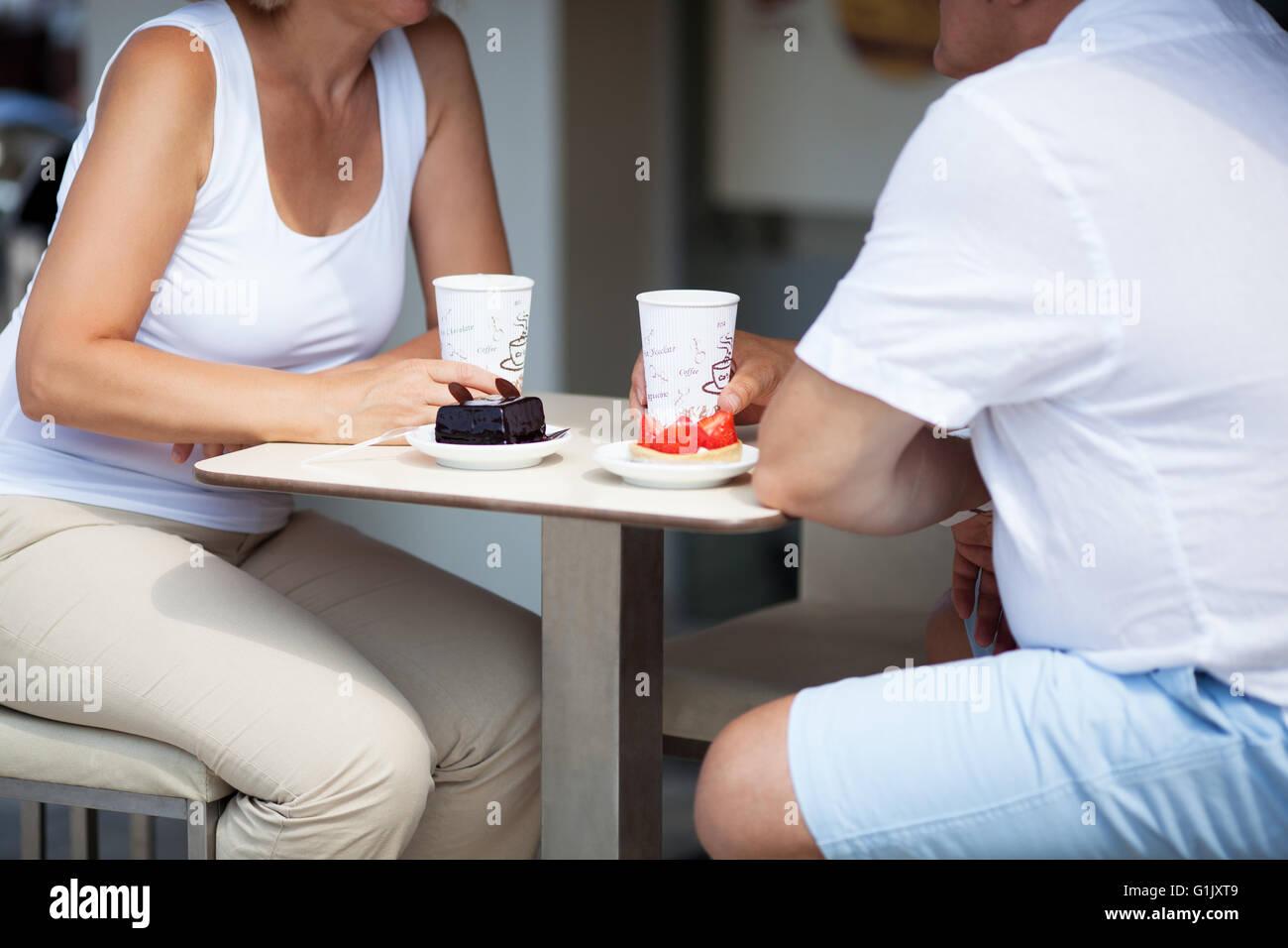 Couple Enjoying Coffee and Desserts on Cafe Patio - Stock Image