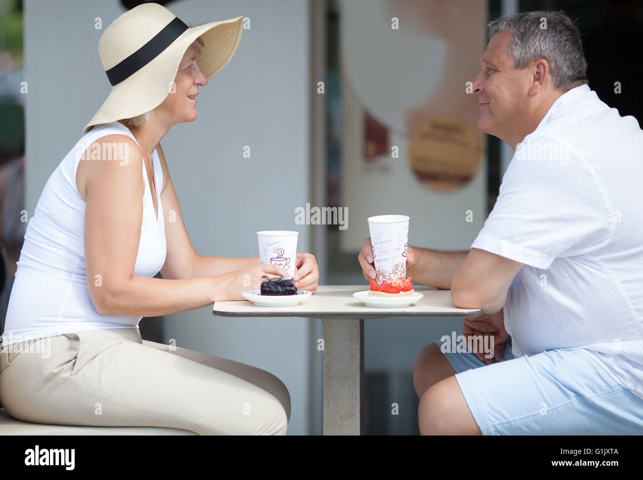 Side view of two smiling elderly people in outdoor cafe - Stock Image