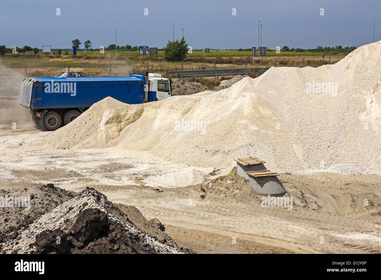 Huge piles of gravel at construction site under bright blue sky. - Stock Image