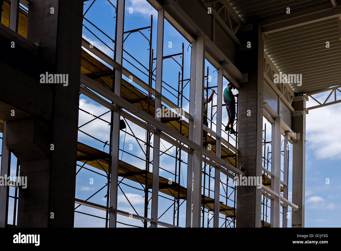 Silhouetted industrial shot with scaffold against blue sky, people are working. - Stock Image