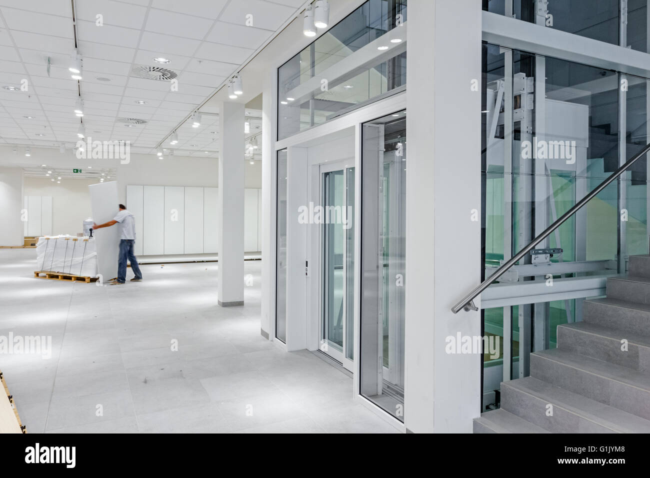 View on staircase and glass elevator in a modern business centre. - Stock Image