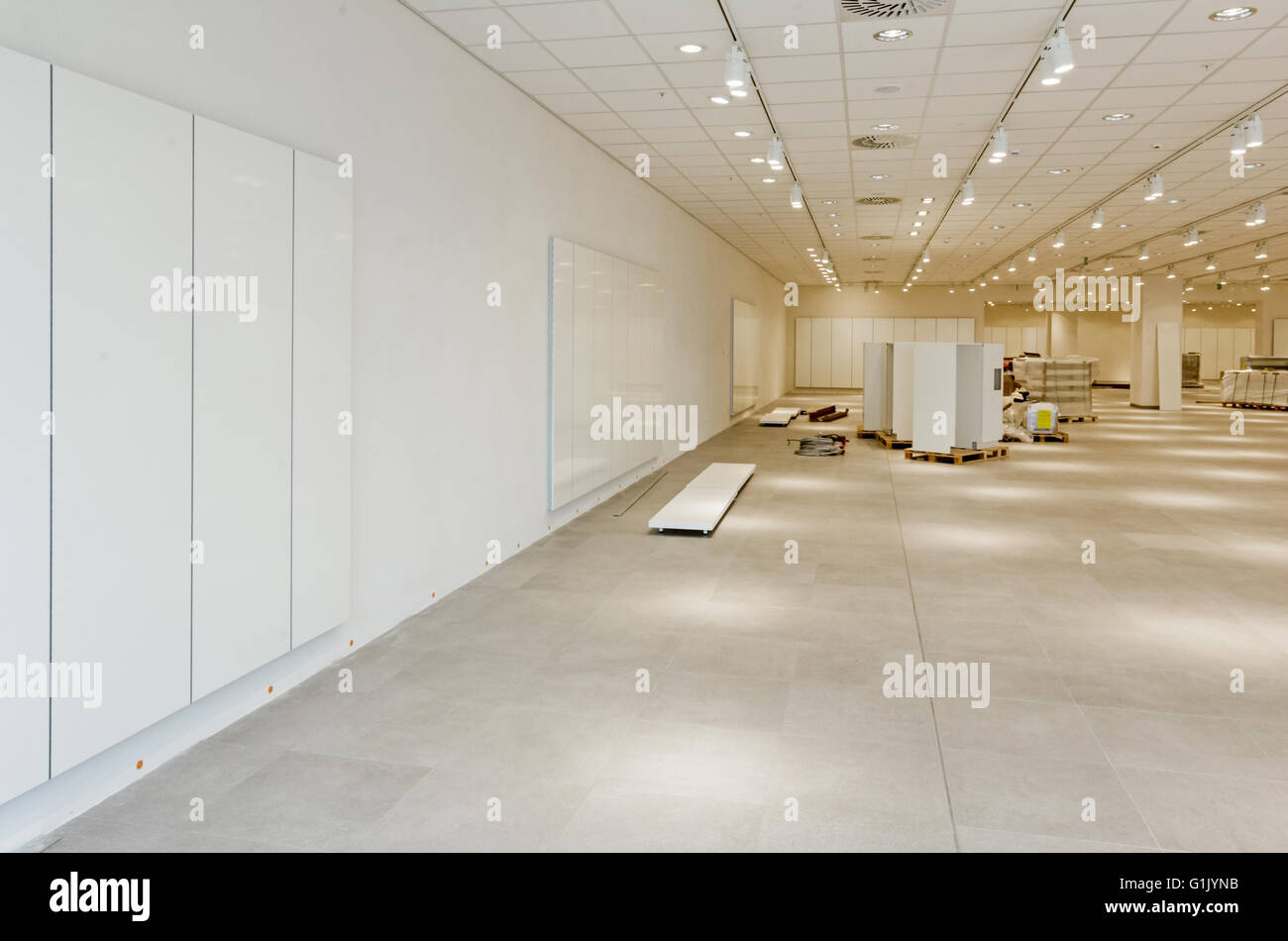 Furnishing equipment is on the floor for white room with ceiling light. - Stock Image