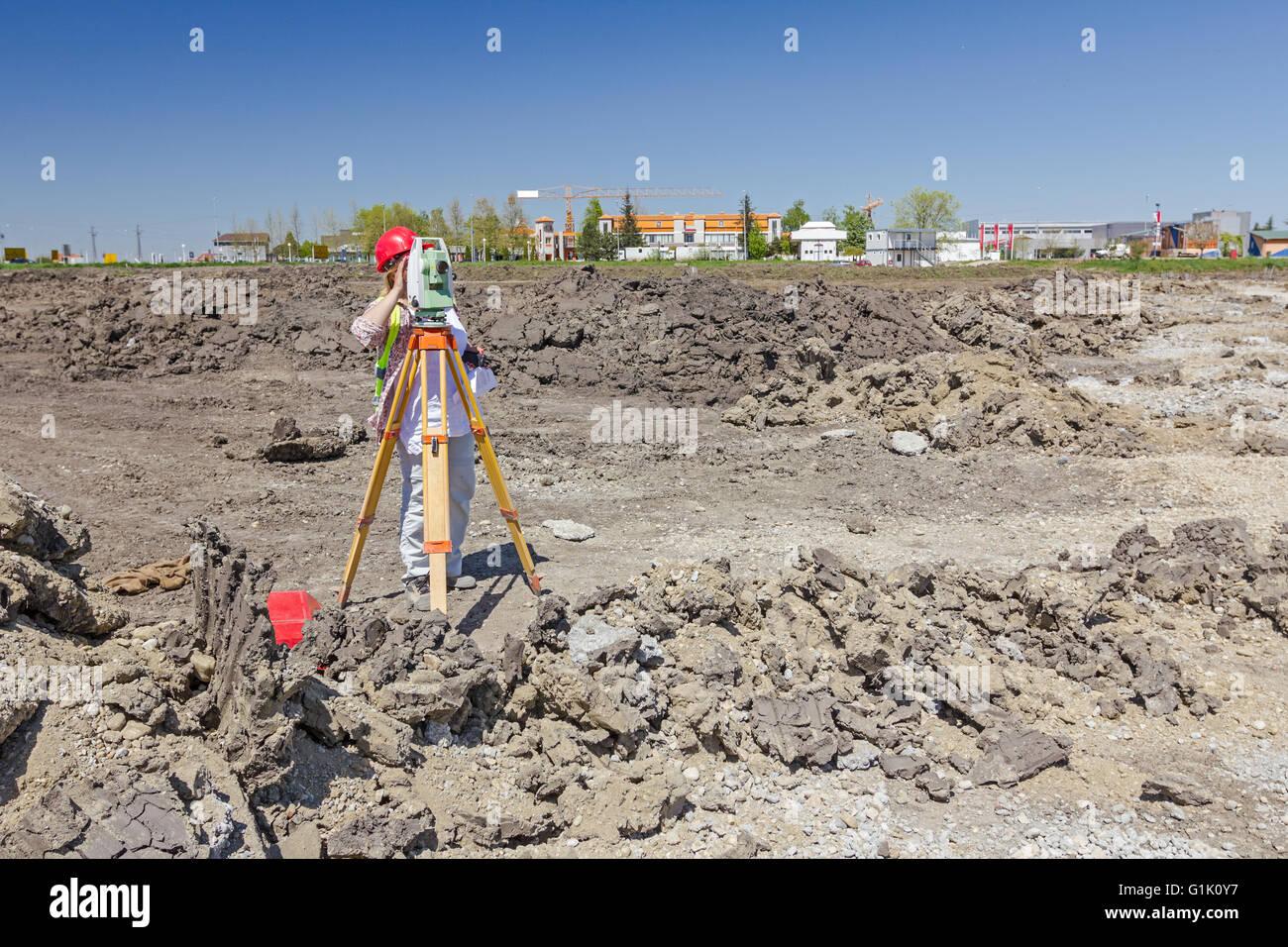 Woman surveying is measuring level on construction site. Surveyors ensure precise measurements. - Stock Image