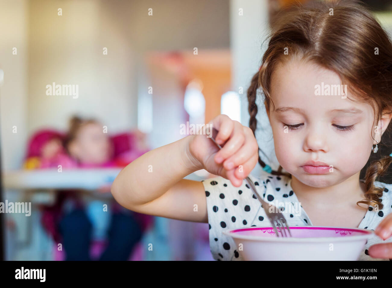 Little girl in the kitchen smiling, eating spaghetti - Stock Image