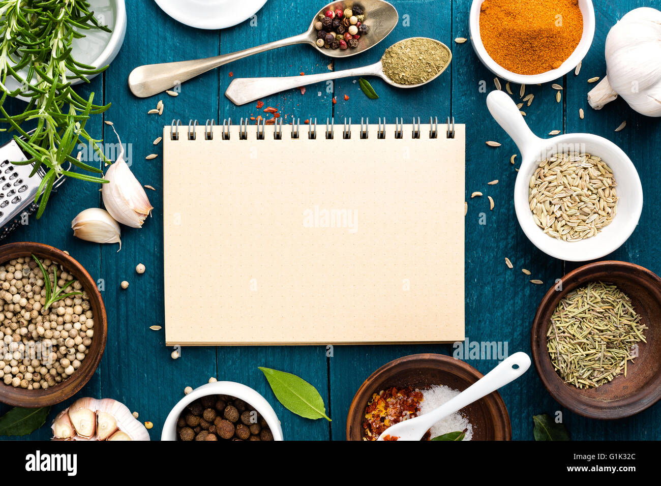 culinary background and recipe book with various spices on wooden table - Stock Image
