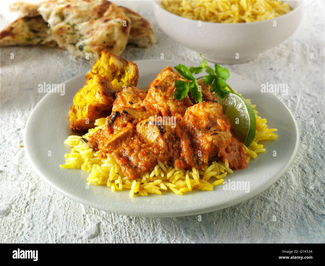 Butter Chicken Asian curry with pilau rice and an onion bhaji - Stock Image