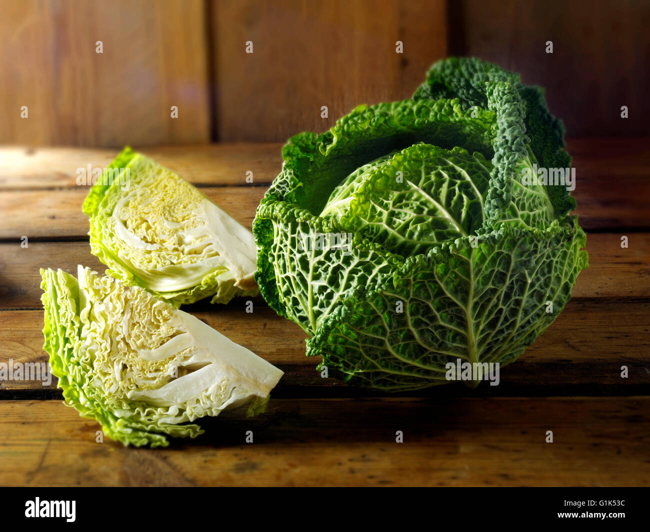 Fresh whole and cut Curly Savoy Cabbage leaves - Stock Image