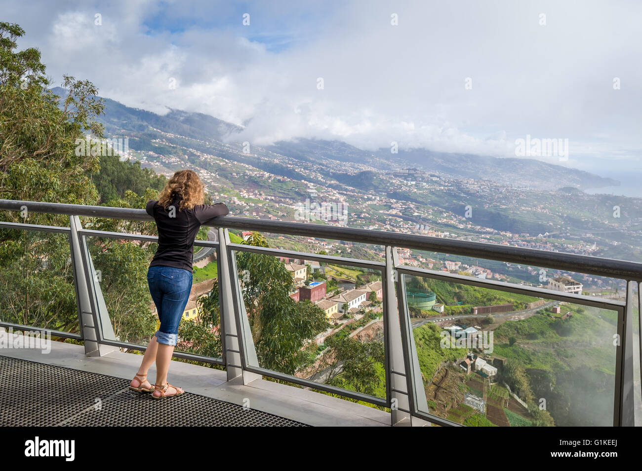 Woman looking at Madeira landscape from Cabo Girao famous viewpoint - Stock Image