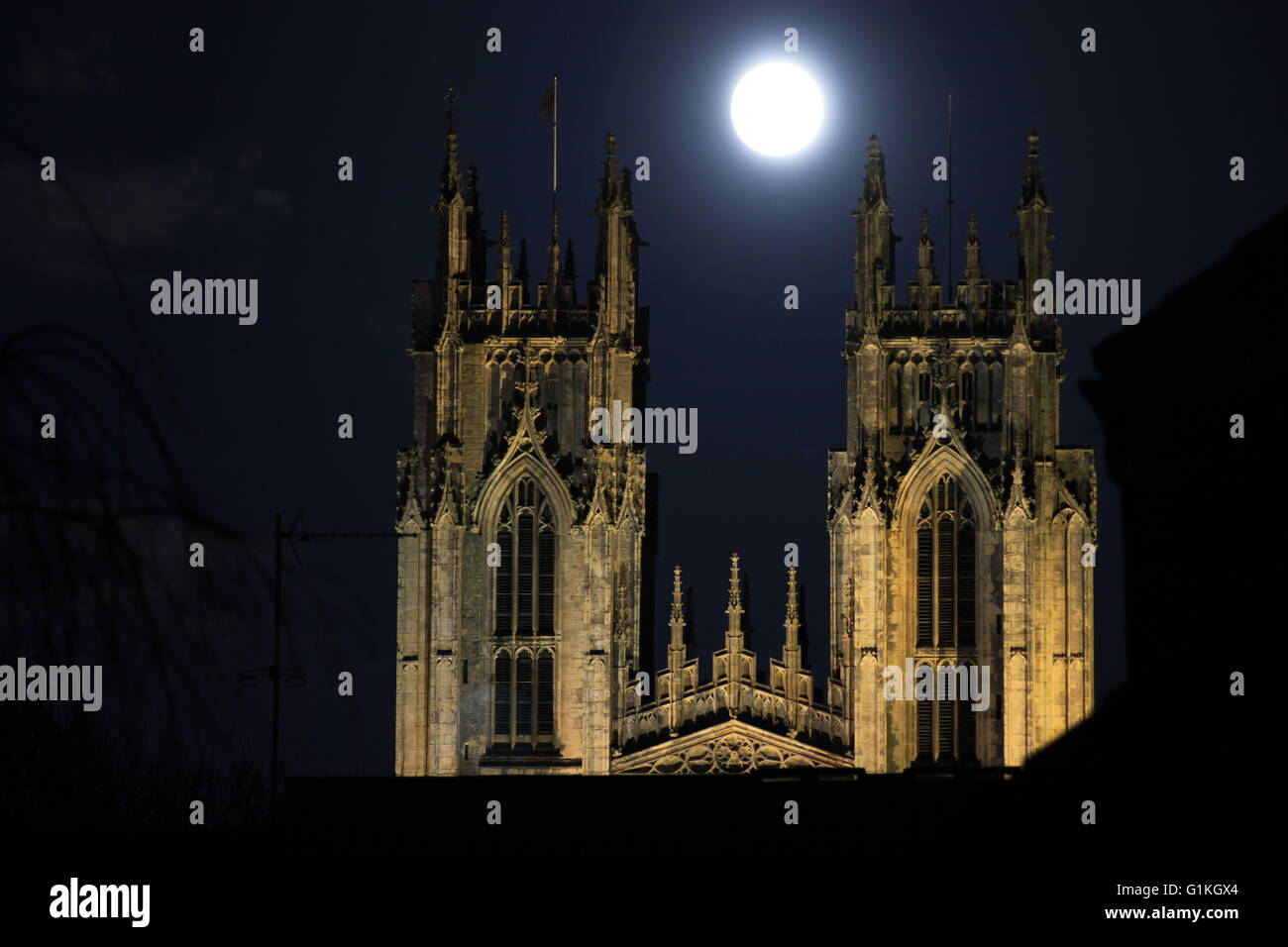 Beverley Minster church Yorkshire with large moon between towers taken after Christmas Eve service dark sky winter - Stock Image