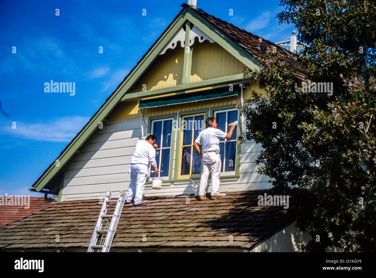 Hispanic men painting historic house in Long Beach, CA Myrleen Pearson - Stock Image
