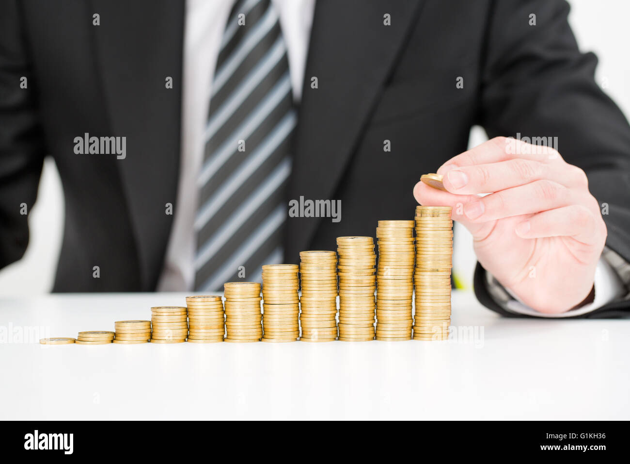 Saving money concept. Businessman hand putting money coin stack growing business. - Stock Image
