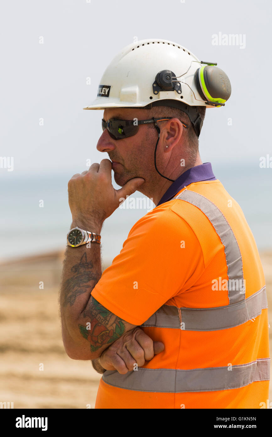 Worker wearing high hi viz vis visibility jacket at Bournemouth beach Stock Photo