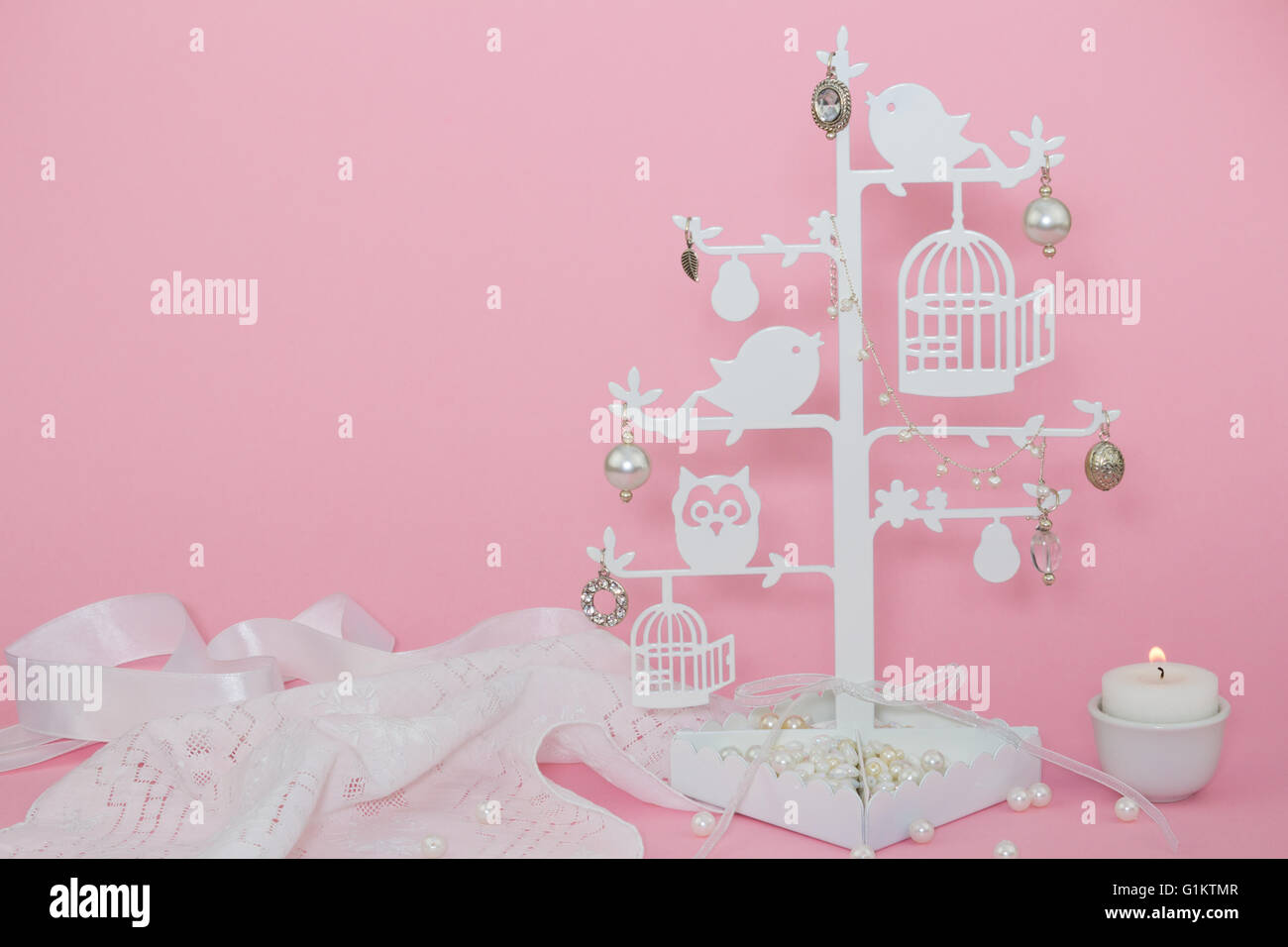 Baby pink invitation background with candle and charms - Stock Image