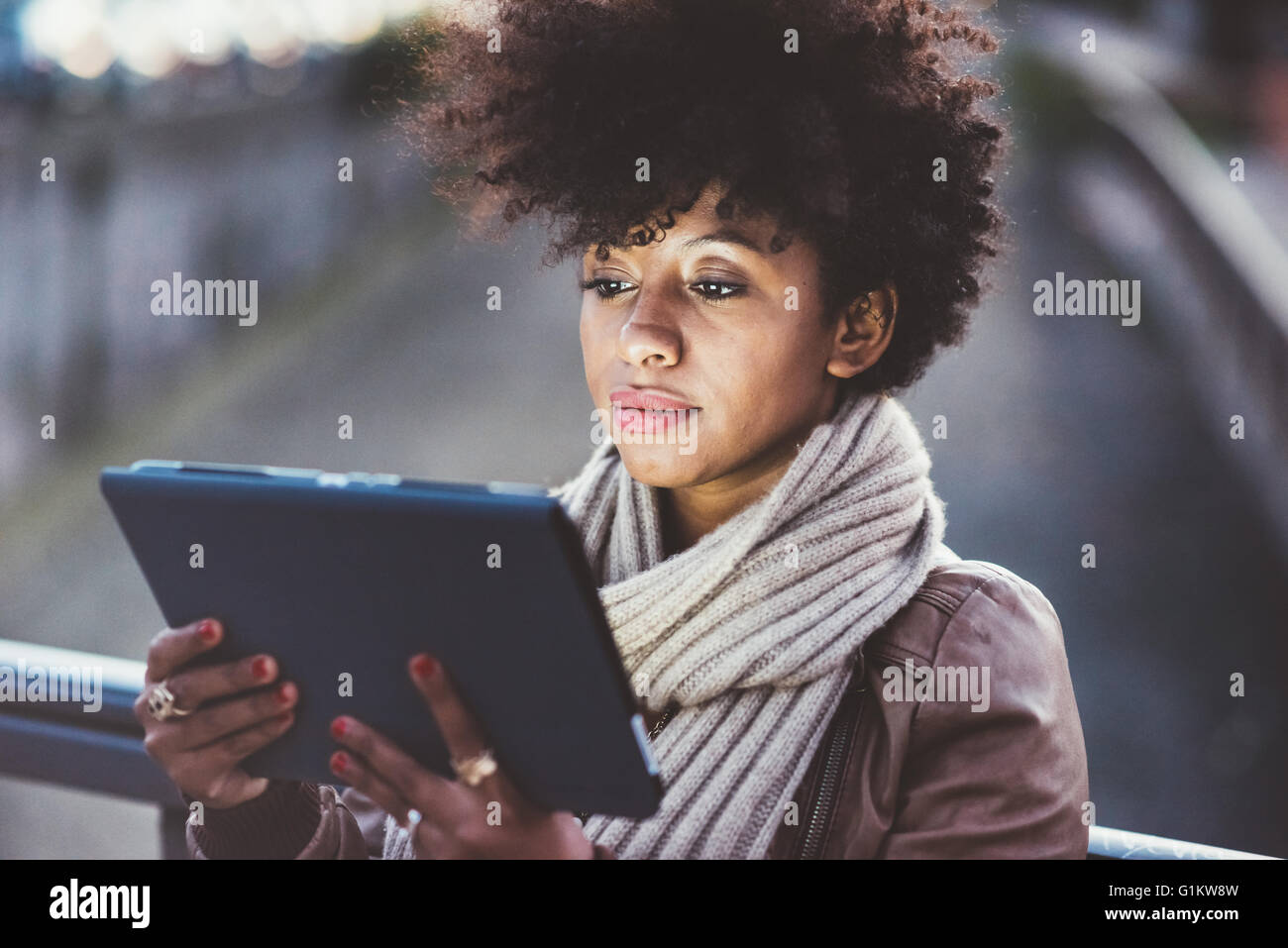 Half length of beautiful black curly hair african woman using tablet in town by night, face illuminated by screen - Stock Image